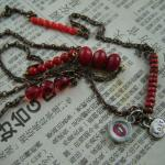 "An interspersed assortment of red glass beads  with ""lust"" charm and ""lips"" charm.  SOLD"