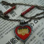 Interspersed czech glass matte red picasso beads with pewter cherub pendant.  SOLD