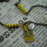 "Interspersed yellow matte picasso czech beads with ""lust"" charm and yellow bottlecap pendant. SOLD"